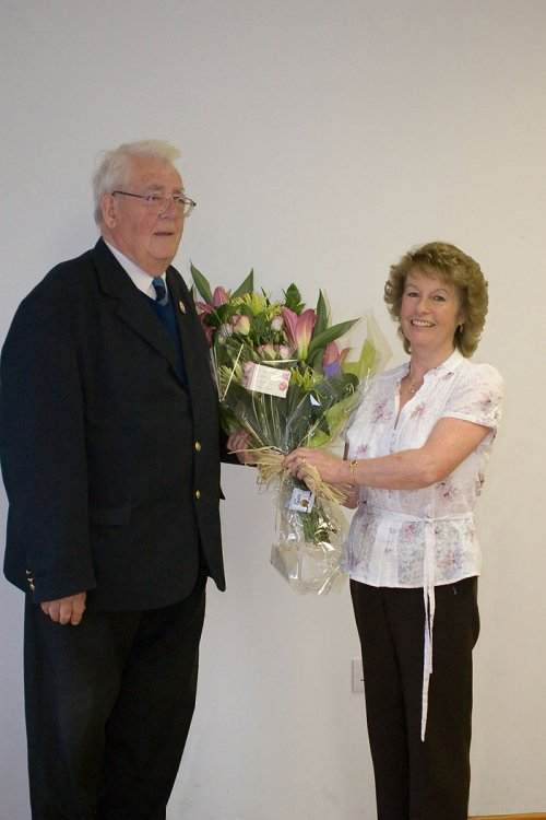 League President Peter McPherson presents Gill Herbert a Bouquet of flowers