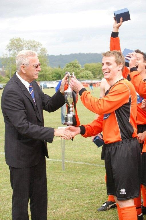 Henbury Captain Eddie Howell receives the Trophy from League Chairman Robin Stewart