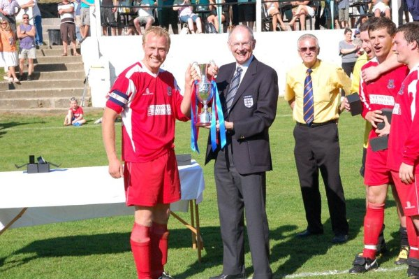 Taverners captain Tom Burridge accepts the cup from FA Joint Chairman Roger Burden